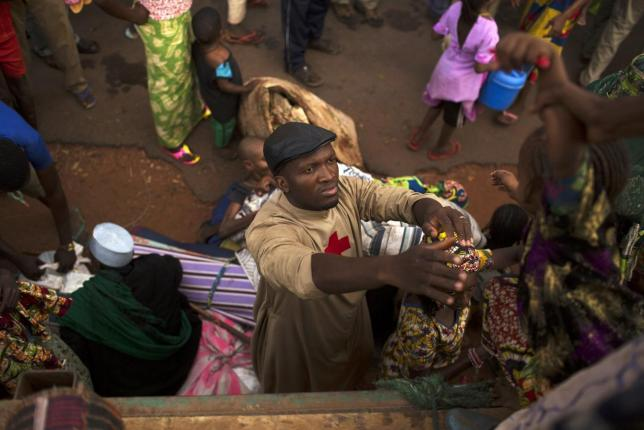 Father Bernard Kenvi (C) helps a Muslim child climb down from an open truck in the town of Bossemptele,